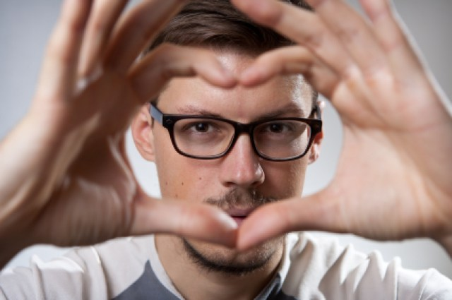 Handsome man with glasses, forming heart shap with hands, looking straight to you through it