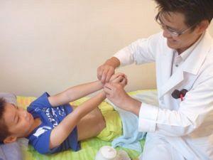 小児はりで脈診する鍼灸師の写真