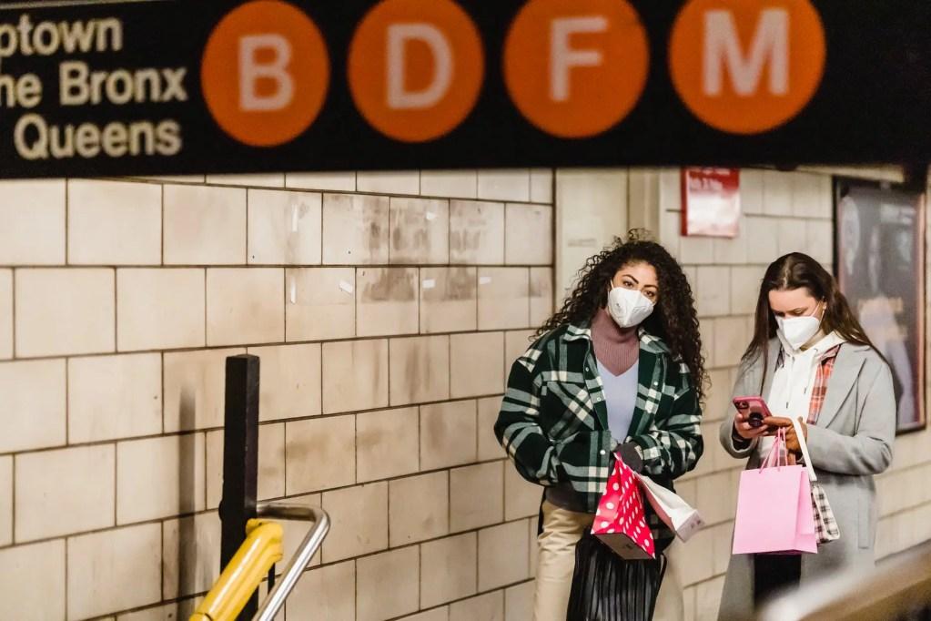 women friends in masks standing in subway passage