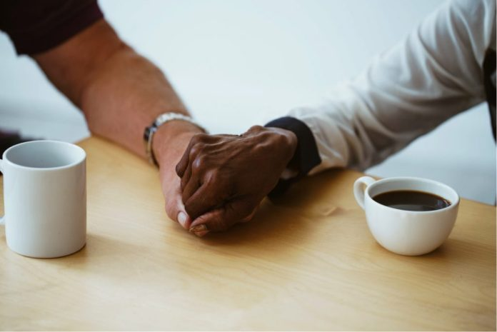 Holding hands while drinking coffee