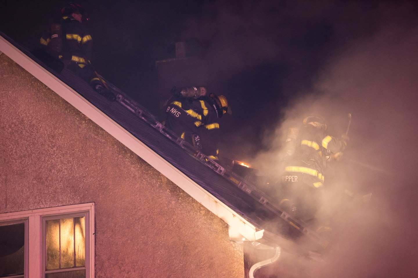 Firefighters working on a roof