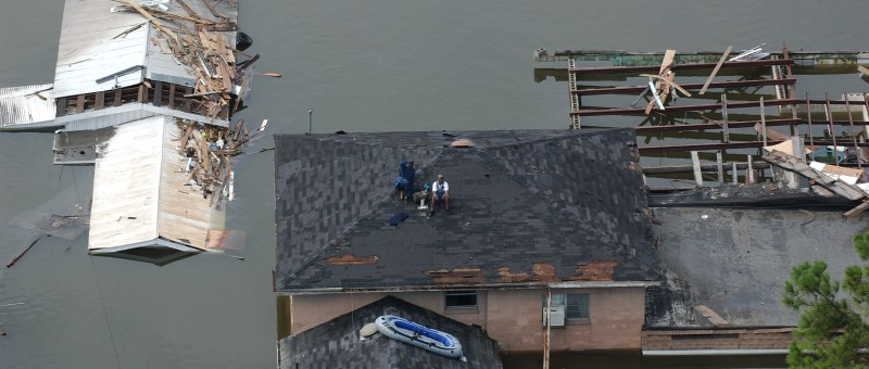 People stranded on top of a home during a flood
