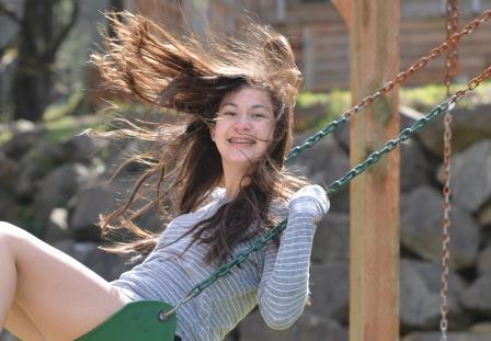 Girl swining on a swing smiling