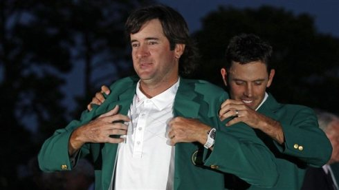 Charl Schwartzel, right, helps Bubba Watson put on the green jacket after winning the Masters on Sunday. Photo taken by Chris O'Meara/AP Photos