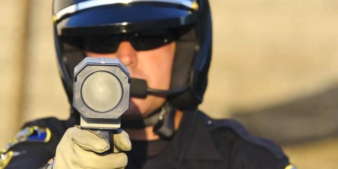 a police officer aiming his radar gun at traffic.
