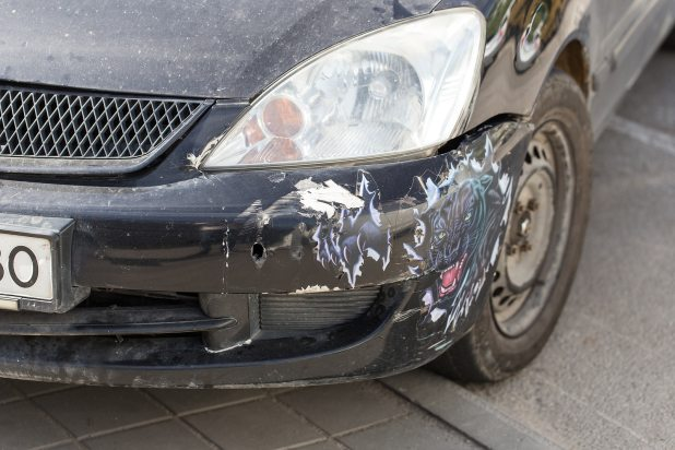 Broken bumper on a black car.