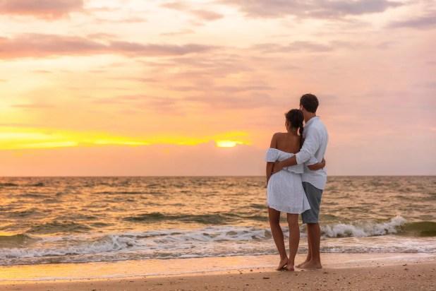 Honeymoon couple walking on sunset