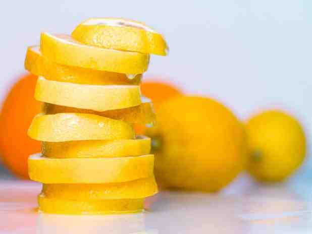 Set of two oranges two lemons and pile of lemon slices