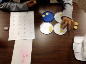 Teaching multiplication with yogurt lids.
