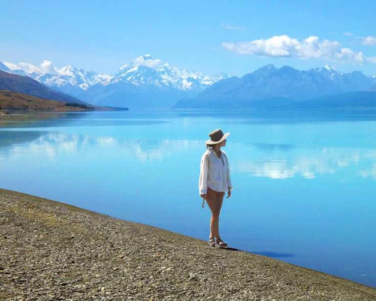 Ellen walking along Lake Pukaki, with reflections of Mt Cook in the background in New Zealand, for Ellen Blazer's travel blog To Travel and Bloom