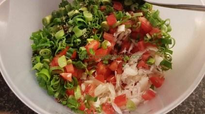 Für die jamainaischen Saltfish Fritters werden Zwiebeln, Lauchzwiebeln und Tomaten feingeschnitten und mit Saltfish (Stockfisch) vermengt.