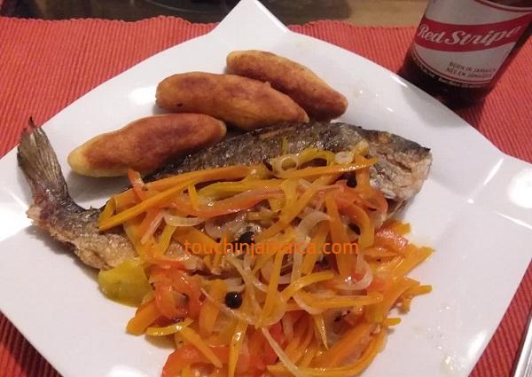 Typisch jamaikanisches Fischgericht mit Essigmarinade und Festival