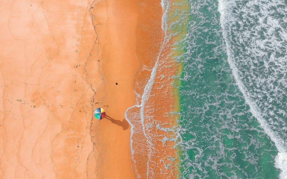 distant unrecognizable person on sandy coast of wavy ocean