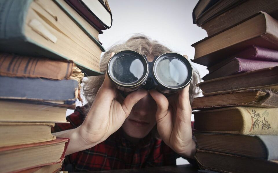anonymous person with binoculars looking through stacked books