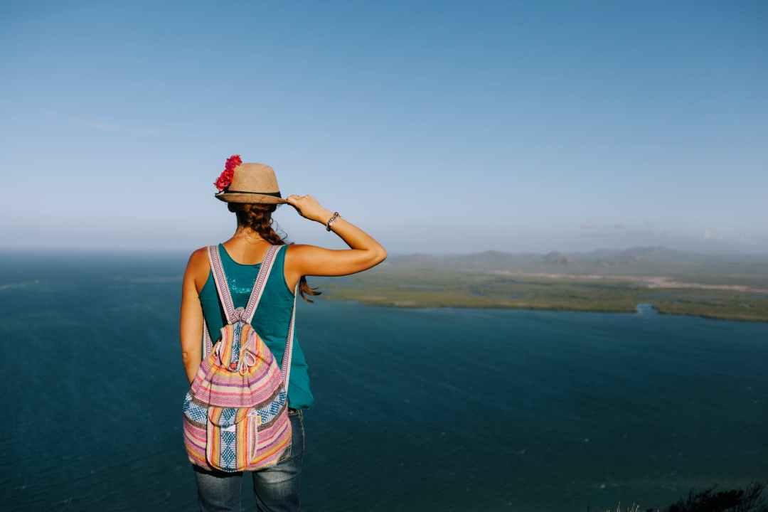 faceless traveler with backpack admiring ocean from mount