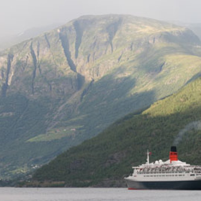 The QE II is dwarfed in the fjord