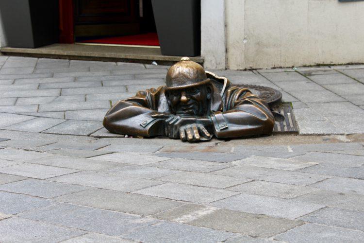 La statue man at work un cheminot qui sort des égouts à Bratislava