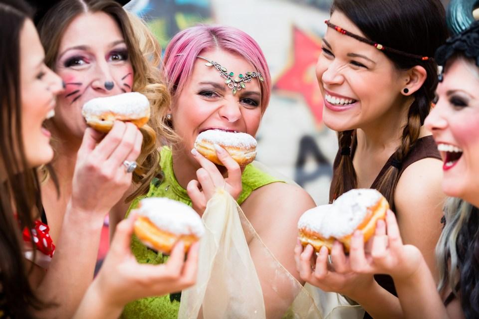 Girls at German Fasching Carnival eating doughnut-like tradition
