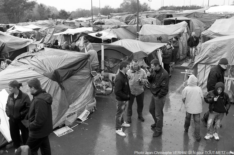 Les familles albanaises, kosovares et bosniaques ont rejoint progressivement le camp de Metz Blida. Les bâches plastique et les toiles de tente sont leurs maisons, séparées par de petites allées.