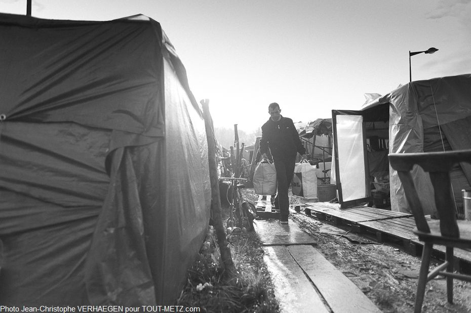 A certains endroits du parking, les allées entre les tentes sont boueuses. Quelques planches glissantes permettent de circuler et d'emmener les bagages au point de départ.