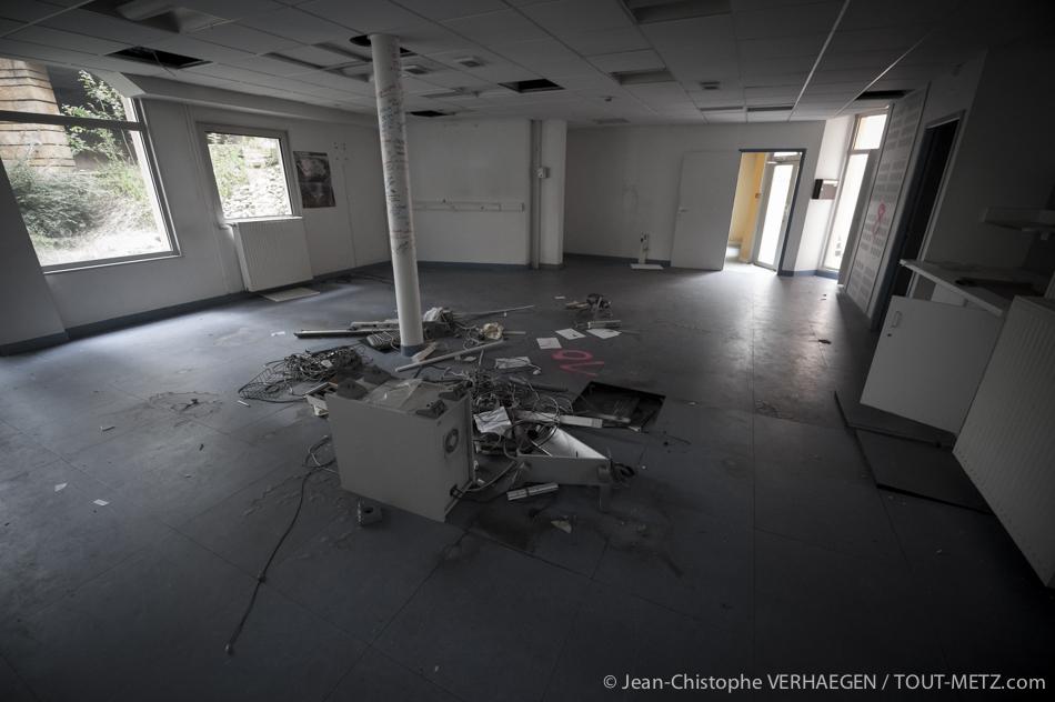 Voici ce qu'il reste du centre d'appel du 15. C'est depuis cette petite salle du rez-de-chaussée qu'étaient gérés l'ensemble des appels aux urgences médicales. Bureaux et personnels étaient disposés autour du poteau central. Bien souvent, les interlocuteurs ne pouvaient pas quitter leur poste de travail et se restauraient sur place.