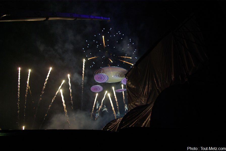Le mobile aérien s'en retourne derrière la scène alors que le spectacle pyrotechnique joue le bouquet final.
