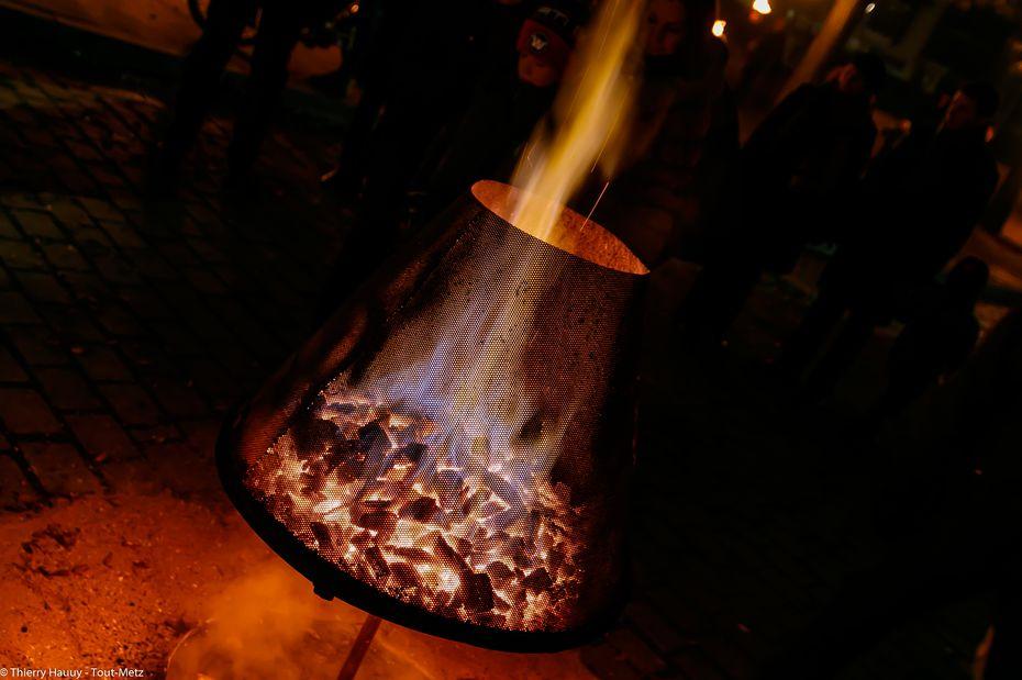 Sur la place devant la salle Fabert, des brûlots éparpillés ont permis de se réchauffer, lors du week-inaugural. Ils participaient au spectacle visuel entre la salle fabert, la cathédrale et la place de la préfecture.