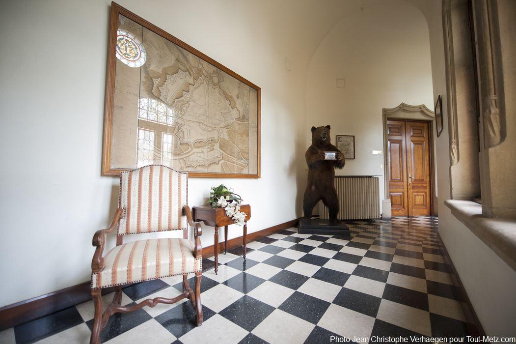 """Dans le couloir principal du rez-de-chaussée trône un ours brun naturalisé. Tué par une compagnie de chasseurs russes, il fut offert en signe d'amitié en 1898. Véritable curiosité des lieux, il permet aux visiteurs des journées du patrimoine de réaliser des """"selfies"""" originaux. Tous les 10 ans, il quitte le palais du gouverneur pour être rempaillé."""