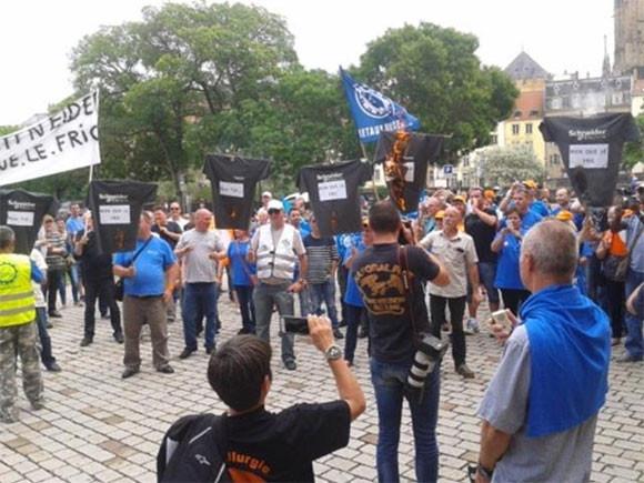 Des t-shirts à l'effigie de Schneider Electric brûlés sur la place par les salariés
