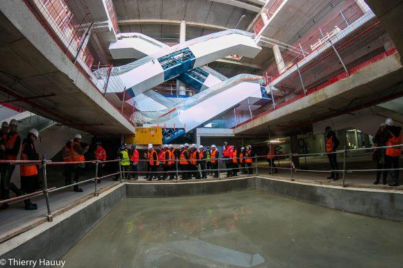 Accès parking vers les escalators. Au sol de l'eau dans ce qui sera un plancher lumineux.