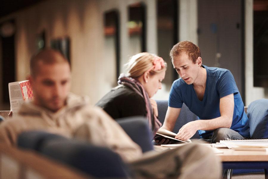 Personas: to unge mennesker i samtale henover en bog - måske studerende?
