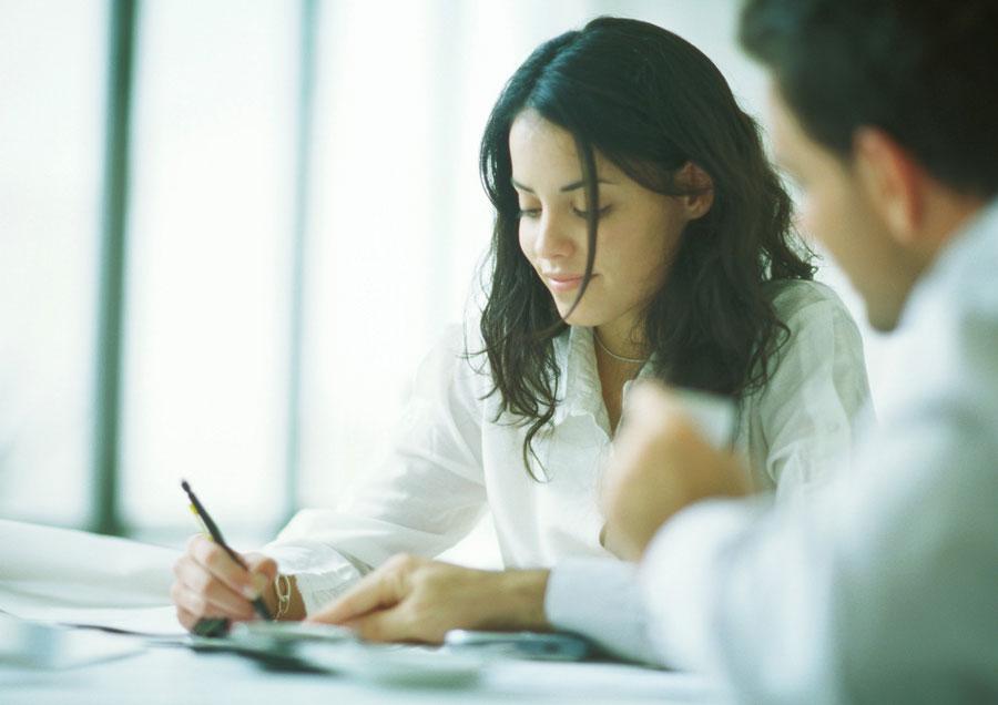 Kvinde, der skriver noter - måske mens hun får feedback, ikke kritik.