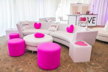 bat-mitzvah-white-curved-couch-with-pink-pillows-pink-ottomans-cube-table-and-white-round-ottoman