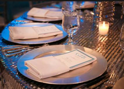 mitzvah-table-setting-silver-striped-tablecloth-silver-charger-plates-personalized-menu-candles-and-chrystal-glasses