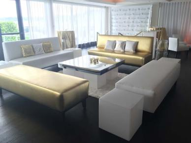 Gold-and-white-lounge-decor-with-sparkle-pillows-and-mirror-table