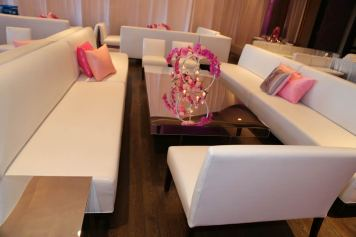 Event-setting-with-white-couches-pink-custom-pillows-mirrored-tables-and-pink-rose-with-silver-rings-candle-holders