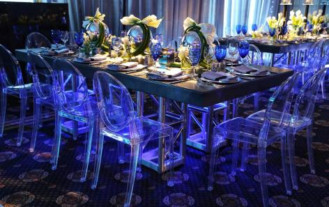 Truss-community-table-with-acrylic-chairs-callililies-centerpieces-and-blue-white-crystal