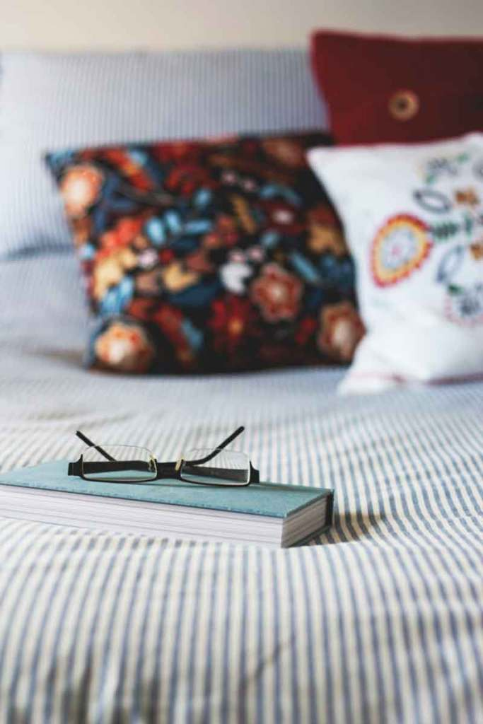 glasses and book on bed
