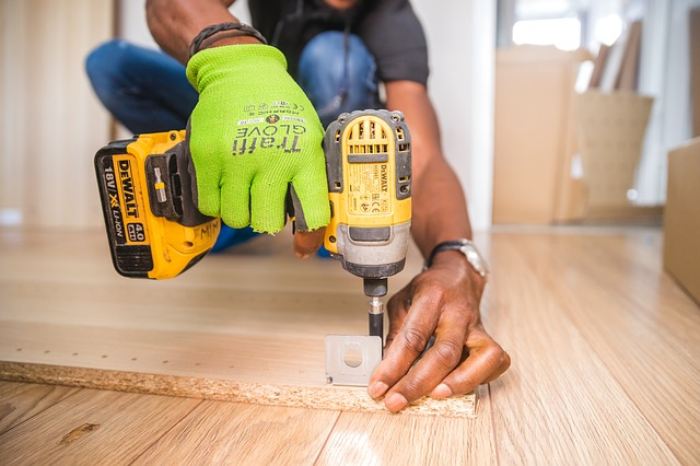 Handyman drilling into floor