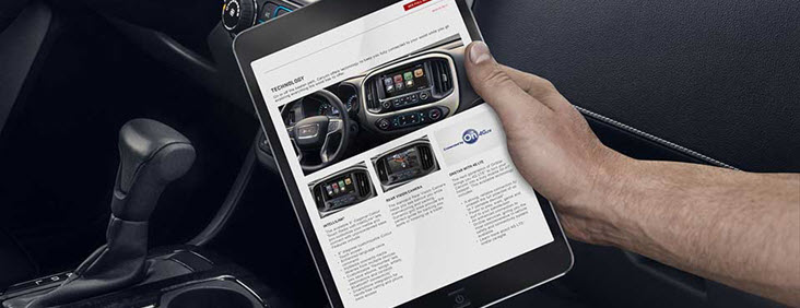 Image of a man's hand holding a tablet connected to the 4G Wi-Fi Hotspot available in the 2017 GMC Canyon pickup truck.