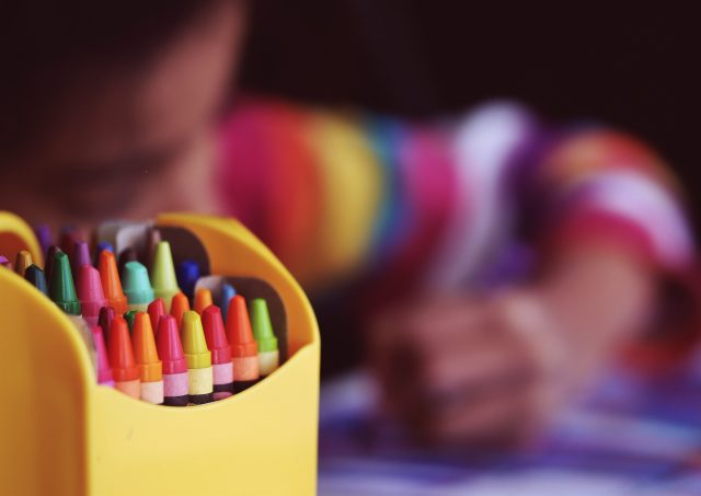 Crayon box in front of a child coloring with coloring page for kids.