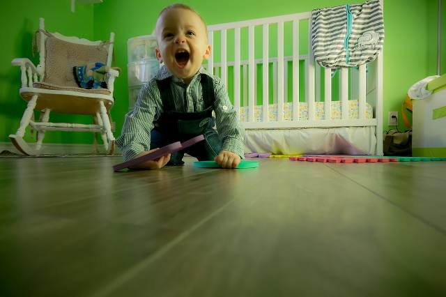 Baby crawling on the floor during play time alone.