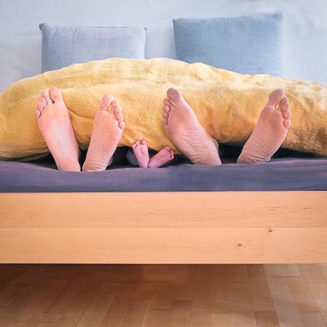 Mom,Dad and little feet at the end of a bed. When will the coronavirus be over? We are all suffering with emotional distress.