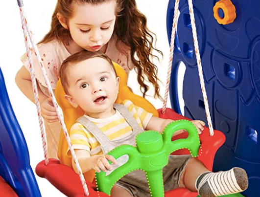 Toddler pushing her baby sibling on a swing which is part of a toddler climbing set. Climbing sets are one of the best toddler toys for physical activity.
