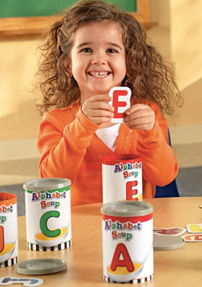 Little girl sorting alphabet letters into a can. She is learning how many letters are in the alphabet.