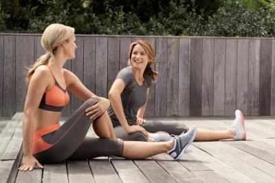 Two women stretching for workout wearing compression clothing.