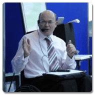 Dr Edworthy is sat in front of an audience gesturing with his hands whilst talking, he has a Trabasack Mini with paper and pen on his lap
