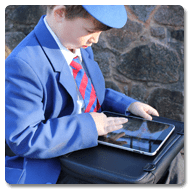Victor is wearing a blue and red school uniform with matching cap, sat outside on stone steps, using an iPad on a Trabasack Mini upon his lap