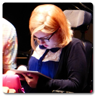 Charlotte has her back to the camera, using a pink trim Trabasack Curve to compose music, whilst surrounded by various musicians with their instruments