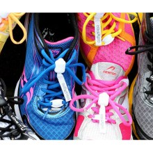 Photograph of several different sports shoes of different styles, fitted with brightly-coloured Greeper Sports shoe laces